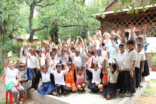 Die Kinder eines Kinderclubs grüßen die Paten in Deutschland. Hier stehen sie um einen von World Vision finanzierten Brunnen mit sauberem Trinkwasser.