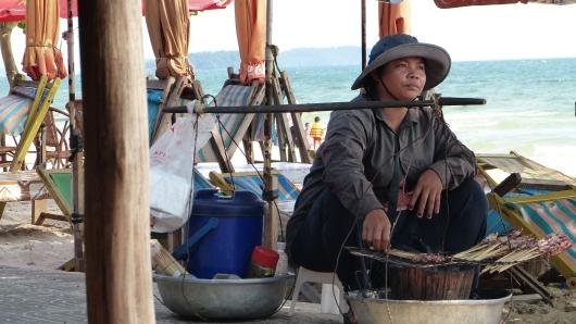 Verkäuferin von frisch gegrillten Tintenfischen am Strand von Sihanoukville