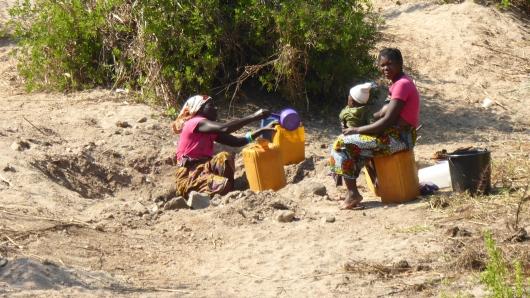in einer abgelegenen Gegend wird Wasser aus einem Wasserloch in einem Flussbett geschöpft